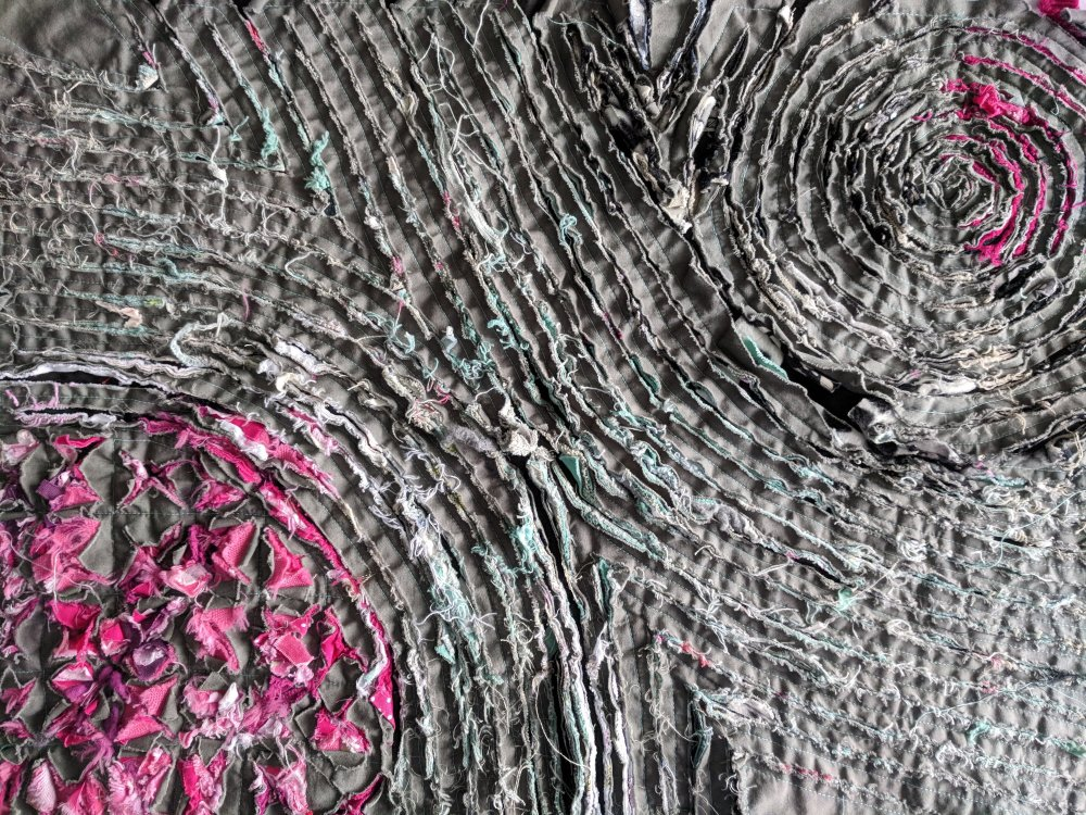 a slashed panel with gret top layer has been stitched  revealing sections of bright pink and muted greens below, several differnt style of stiching and cutting are visible, squares, spirals and lines.