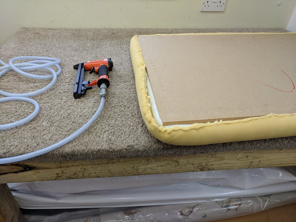 Workbench with staple gun and uncovered footstool lid