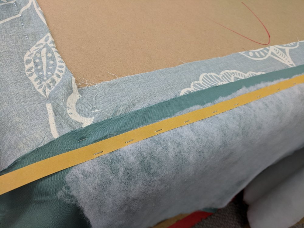 Cardboard strip is stapled over wadding and lining fabric