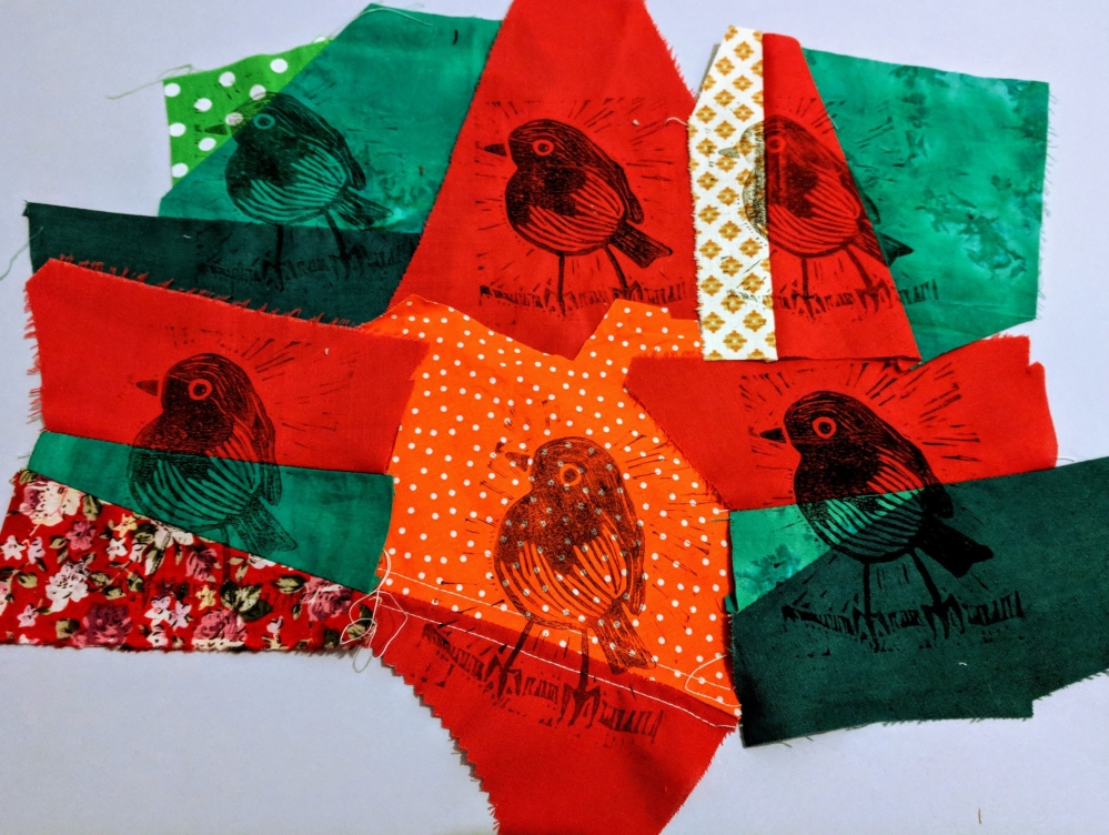 Collage of lino printed robins on patched fabrics